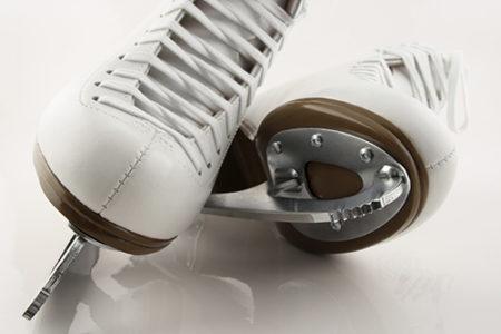 Blades of white figure skates.